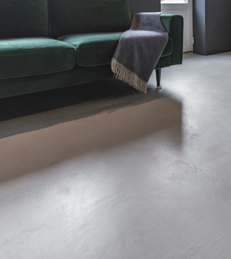 light grey micro cement floor capturing the low angle light with green sofa in background